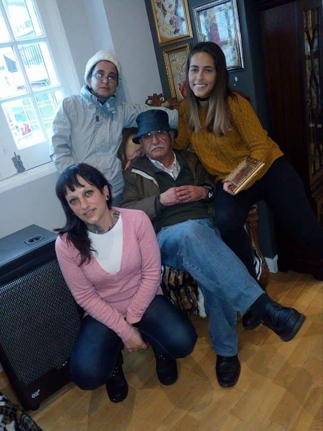 Pai sentado na poltrona com filhas e Gaby.